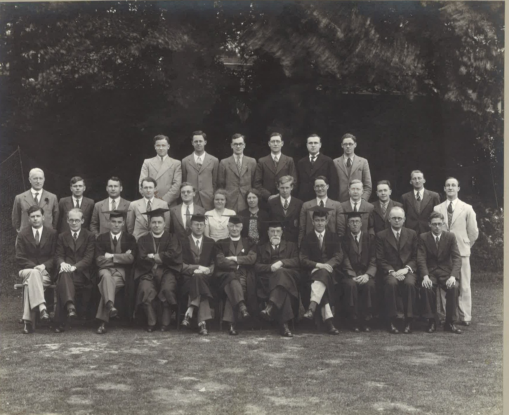 A monochrome College photograph of Mansfield students in 1939. There are two women in the large group of men. The front row is mainly academics wearing mortar boards, the rest wear suits.
