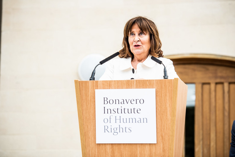 "Helena Kennedy stands at a podium making a speech. The podium has a sign on it reading ""Bonavero Institute of Human Rights"" and microphones on the top. Behind her you can see the white wall and wooden main door of the Mansfield Garden Building."