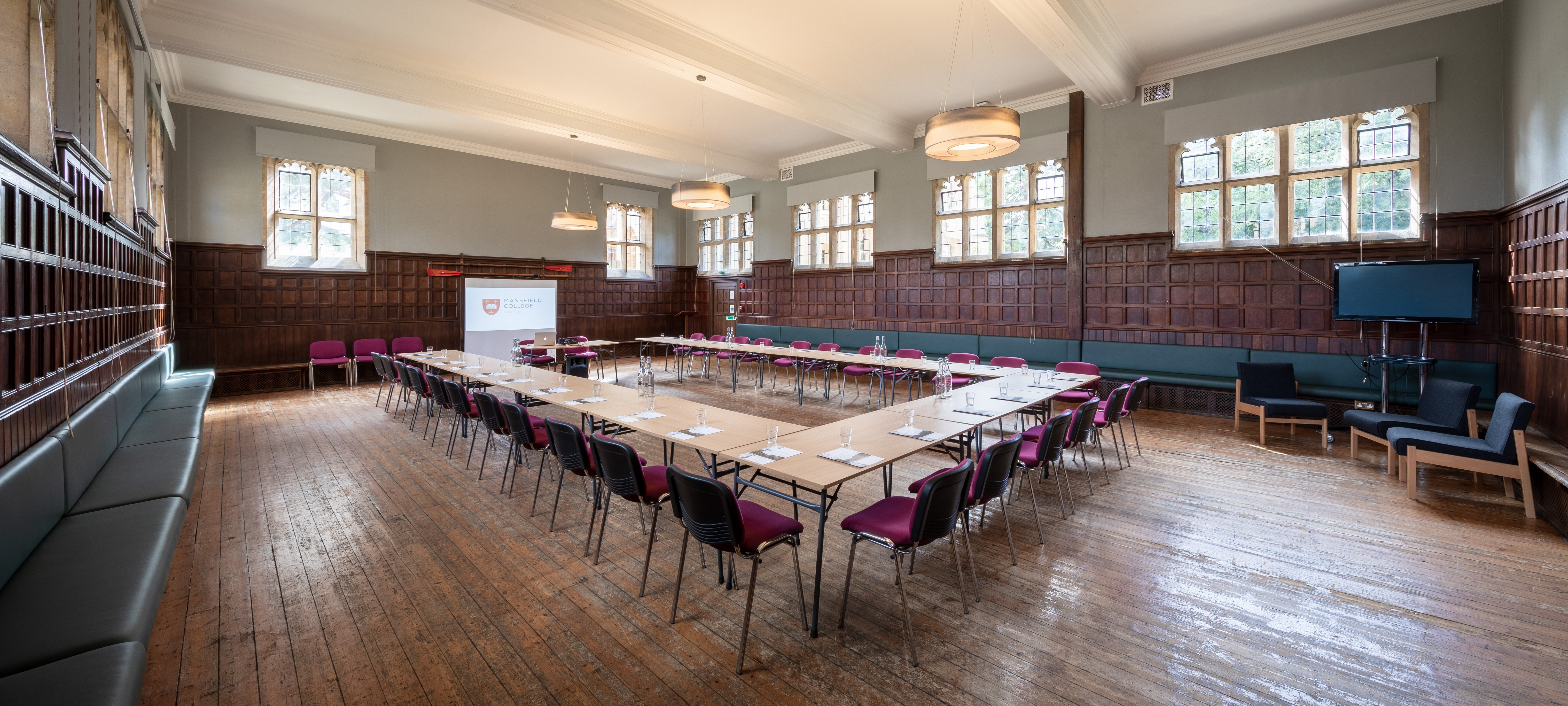 The JCR at Mansfield College, with high windows, half wood-panelled walls and a wooden floor.