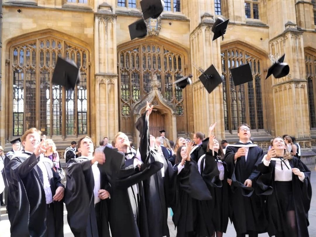 Graduates in academic dress throwing their mortar boards in the air outside the Sheldonian Theatre.