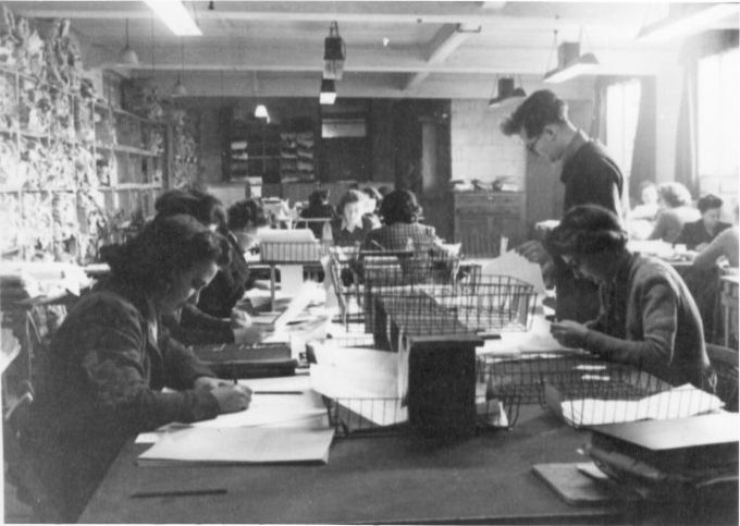 A code making room at Bletchley Park. Rows of code makers sit with papers and in-trays in front of them, all concentrating on writing, sitting on tables of four in a long room.