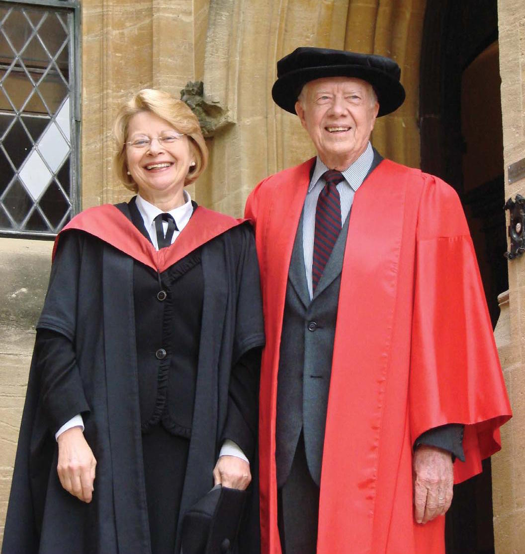 A smiling Diana Walford poses for a photo alongside the Vice Chancellor of the University of Oxford. They both are dressed in red academic dress. The photo is taken on the steps of the Principal's Lodgings, with yellow sandstone buildings behind them.