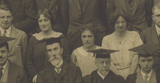 A close up of a section of a group photograph. The front row are all men, wearing suits, gowns and mortar boards. Many are old and bearded. In the row behind them are three lone women amongst all the men.
