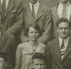 A close up of one woman among lots of men, all dressed formally, in a group photograph