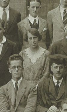 A woman surrounded by men in a monochrome group photograph