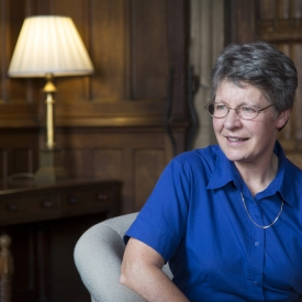 A headshot of Jocelyn Bell Burnell. She sits in the Mansfield SCR, with it's wood paneled walls and a lamp on a table in the background.