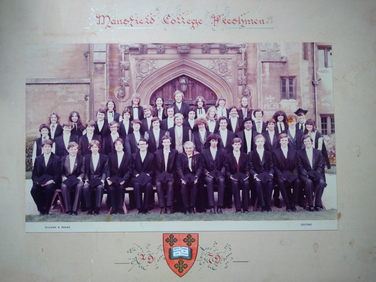 "A year group matriculation photograph from 1979.  It is a colour photograph. The students wear academic dress. There are a small number of women in the group. The photo has a white frame around it: at the top it says ""Mansfield College Freshmen"" and at the bottom there is the Mansfield shield and the date ""1979""."