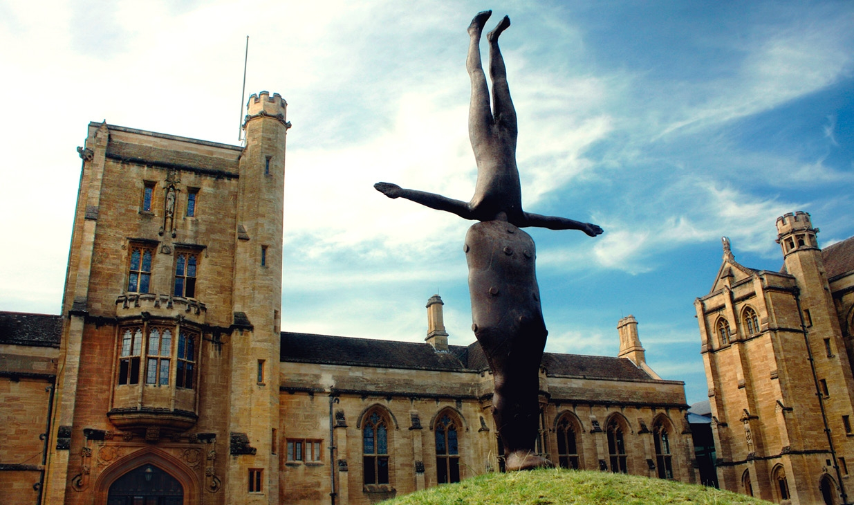 A low angle shot of the Mansfield main building with blue skies. In the foreground is Anthony Gormley's 'Present Time' sculpture, which sits in the middle of the quad. The statue is cast from the artist's body, with arms outstretched. The statue has a reflection effect, as one of the torsos sits normally below the head, but the other rises above the torso.