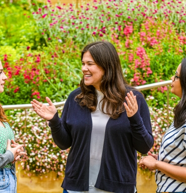 Three students stand chatting with the bright green and pink of the flower beds behind them.