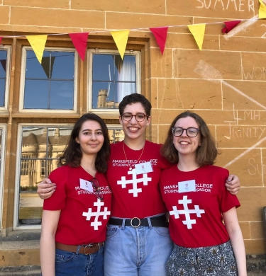 Three student access ambassadors wearing matching red tshirts with the Mansfield cross logo on it. They are at an open day. Red and white bunting hangs above them - the Mansfield colours. They stand in front of the John Marsh building, which has rowing results faintly chalked to the wall.