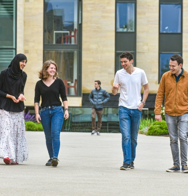 Four post-graduate students walking in a line by the Hands building