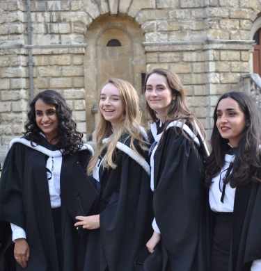 Four women in their graduation gowns pose for an informal photo outside the Radcliffe Camera.