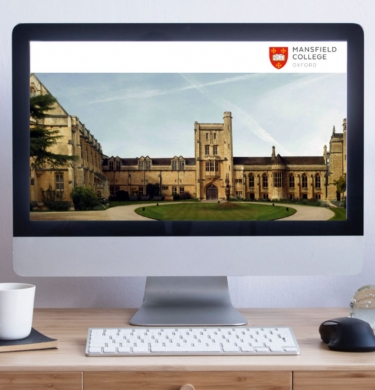 A desk with a computer screen on it. On the screen is an image of Mansfield college with the logo in a banner at the top. A plant pot and a desk plant flank the screen.