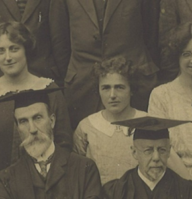 Dorothy Wilson pictured centrally in this close up shot of a year group photo. In the foreground row are men in academic dress. Behind them, three women.