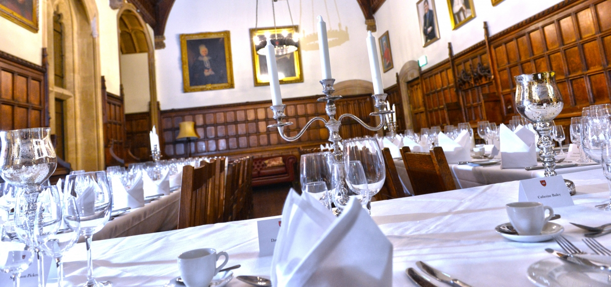 Tables are set for a formal meal in a large, half-panelled room.