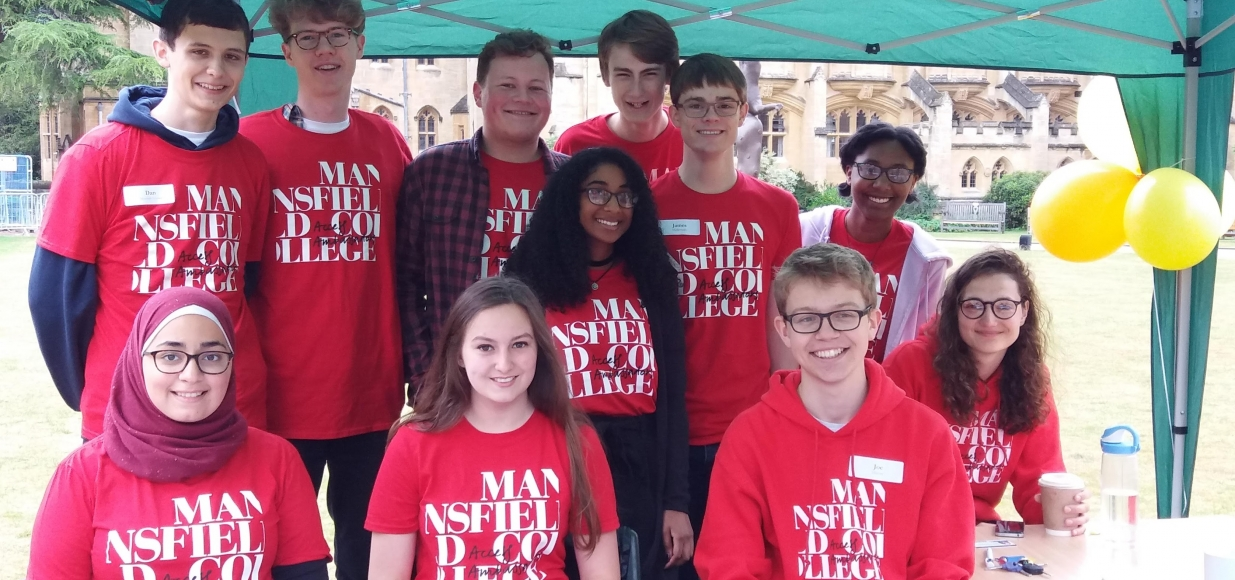 A group of Mansfield student Ambassadors all wearing matching red t-shirts at an open day. They are standing under a gazebo with balloons on the quad.