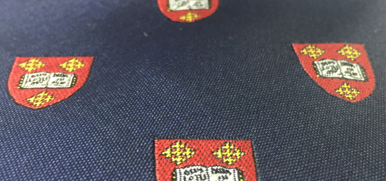 A close-up of a Mansfield College silk tie with a repeat pattern representing the College crest