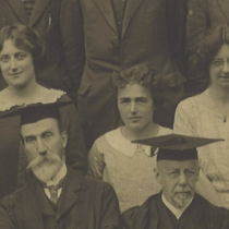 Dorothy Wilson pictured centrally in this close up shot of her in the year group photo. In the foreground row are men in academic dress. Behind them, three women.